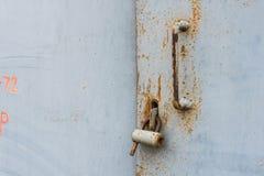 Die alte Tür schloss mit hängenden Klammern eines Vorhängeschlosses zu Satz Hintergründe Stockbild