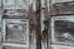Die alte Tür schloss mit hängenden Klammern eines Vorhängeschlosses zu Schräg Stockfotos