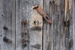 Die alte Tür schloss mit hängenden Klammern eines Vorhängeschlosses zu Schräg Stockfoto