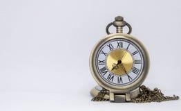Die alte Taschenuhr ist eine Halskette, die auf dem weißen Boden gelegen ist, der getrennt wird lizenzfreies stockbild