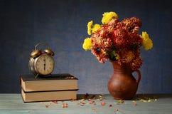 Die alte Uhr, die Bücher und die Blumen in einem Vase Lizenzfreie Stockfotos