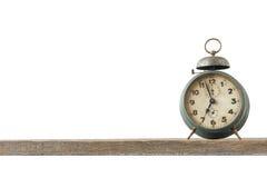Die alte Uhr mit einem Wecker ist auf dem Brett Lizenzfreie Stockbilder