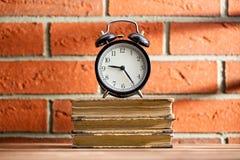 Die alte Uhr und die alten Bücher Stockfotos