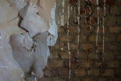 Die alte und ruinierte Backsteinmauer mit Gips, verlorene Plätze Stockfotografie