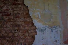 Die alte und ruinierte Backsteinmauer mit Gips, verlorene Plätze Stockbild
