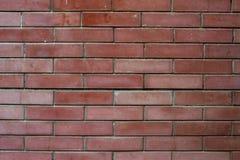 die alte Wand des roten Backsteins mit Sprüngen, städtischer Hintergrund, Beschaffenheit Stockfotografie