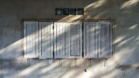 Die alte Zementbacksteinmauer mit den hölzernen Fenstern Lizenzfreie Stockbilder