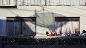 Die alte Zementbacksteinmauer mit den hölzernen Fenstern und der Schatten der Satellitenschüssel Lizenzfreie Stockfotografie