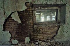 Die alte zerstörte Backsteinmauer in der Stadt von Pripyat: grüner Gipsfall weg von den Schichten, Fenster mit schmutzigem Glas,  Lizenzfreie Stockfotografie