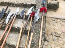Die alten alten mittelalterlichen kalten Waffen, Äxte, Halberds, Messer, Klingen mit Holzgriffen lecken auf den Steinschritten de lizenzfreie stockfotos