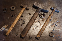 Die alten Stahlhämmer mit Holzgriffen und einigen Bolzen, Nüsse, Lager, Ventile, Waschmaschinen, Nägel auf dem Metallhintergrund Stockbild
