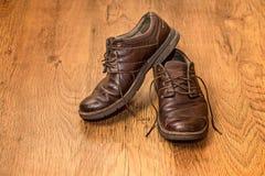 Die alten Stiefel der Männer auf hölzernem Hintergrund Lizenzfreie Stockfotos