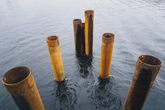 Die alten verrosteten Rohre im Wasser Stockfoto