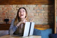 Die amerikanische blonde weibliche Person, die Gesichter mit den Zeigefingern macht, nähern sich Laptop Stockbild