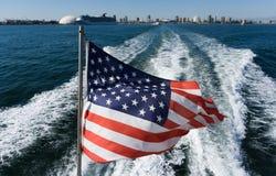Die amerikanische Flagge fliegt auf der Rückseite des Bootes Ansicht vom Boot auf der amerikanischen Flagge und der Stadt Stockfotos