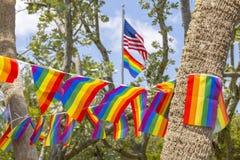 Die amerikanische Flagge fliegt hoch über die Fahne der Flagge des homosexuellen Stolzes stockbild