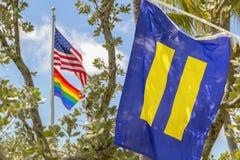Die amerikanische Flagge fliegt hoch mit der homosexueller Stolz- und Gleichheitsflagge lizenzfreie stockfotografie