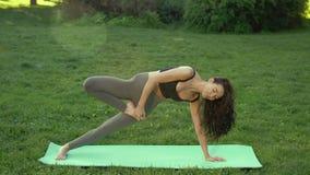 Die Anfängereignungsfrau, die Yoga durchführt, wirft schwierige Übung oben tun draußen schnell geben auf stock video footage
