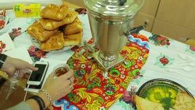 Die angemessene Nächstenliebe, gießt Tee von einem Samowar stock footage