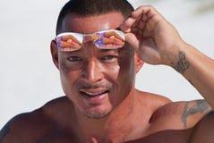 Die anhebenden Sonnenbrillen des Mannes, zum heraus zu überprüfen setzen Schätzchen auf den Strand Lizenzfreie Stockfotografie