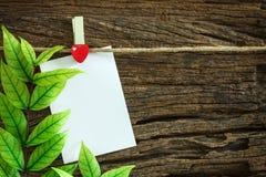 Die Anmerkung des leeren Papiers, die durch rotes Herz hängt, befestigt auf hölzernem Hintergrund Lizenzfreie Stockfotografie