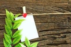 Die Anmerkung des leeren Papiers, die durch rotes Herz hängt, befestigt auf hölzernem Hintergrund Lizenzfreie Stockfotos