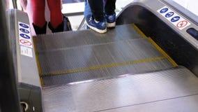 Die anonymen Leute, die auf die Rolltreppe gehen, heben in Einkaufszentrum an stock footage