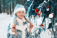 Die Ansammlungs-Puppe Porträt eines kleinen Mädchens mit Zöpfen im Wald nahe dem Baum des neuen Jahres Abstrakte Fantasiehintergr lizenzfreies stockbild