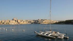 Die Ansicht über Valletta und das Segel yacht mit ukrainischer Flagge im Sonnenuntergang stock footage