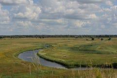 Die Ansicht des Flusses und dieses gelben Feldes vom Hügel am sonnigen Tag des Sommers Lizenzfreie Stockfotografie