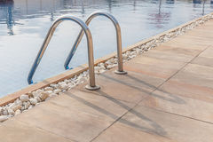 Die Ansicht des metallischen Leitereingangs, zum des blauen Swimmingpools zu klären Lizenzfreie Stockfotos