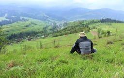 Die Ansicht des Reisenden der malerischen Landschaft der Karpatenberge und des Dorfs im Tal, eingehüllt in Nebel stockfotos