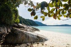 Die Ansicht durch die Blätter auf Felsen auf weißem Sand Schildkrötenstrand Lizenzfreies Stockfoto
