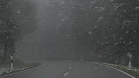 Die Ansicht vom Auto, das auf eine Gebirgsstraße während Schneefälle reitet stock video