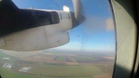 Die Ansicht vom Fenster eines hellen Flugzeuges auf einer Maschine mit drehenden Propellerblättern stock video