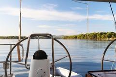 Die Ansicht vom Heck einer Segeljacht ausgerüstet mit zwei Handrädern auf einem schönen Green Bay mit einem felsigen Ufer und ein stockfotografie