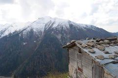 Die Ansicht von den Bergen bedeckt mit etwas Schneehintergrund und einem Häuschen in Region Schwarzen Meers Lizenzfreie Stockbilder