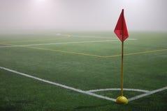 Die Ansicht von der roten Eckflagge auf einem Fußballplatz im Nebel Stockfoto