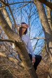 Die Ansicht von unten, die nettes dünnes Mädchen bezaubert, ist auf ungewöhnlichen Baum ohne Blätter auf Hintergrundhimmel stockfotografie
