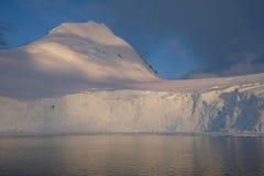 Die Antarktis-Ruhemitternachtssonnenuntergang auf schneebedecktem Berg stockfotos