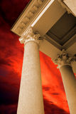 Die antiken Spalten auf dem roten Himmelhintergrund Lizenzfreie Stockfotos