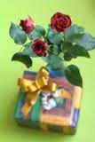 Die anwesende Sitzung, Blumenstrauß von drei Rosen mit Geschenk-Kasten auf Hintergrund Stockfotos