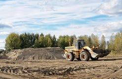 Die Arbeit des Traktors in einer Sandgrube Lizenzfreies Stockfoto