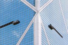 Die Arbeitsbühnen, die durch Seile auf der Seite eines Wolkenkratzers hängen Lizenzfreie Stockfotografie