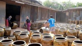 Die Arbeitskräfte, die Drachen rollen, entwerfen Gläser aus Brennofen in der Tonwarenindustrie heraus an Ratchaburi-Provinz stock footage