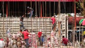 Die Arbeitskräfte erledigen manuelle Arbeit Eimer Frischbeton werfend, wenn sie ein Schulgebäude konstruieren stock video