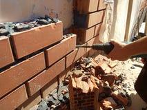 Die Arbeitskraft baut die Wand durch einen Hammer in einem Landhaus ab lizenzfreie stockfotos