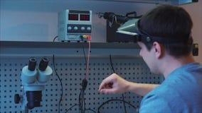 Die Arbeitskraft benutzt die Laborstromversorgungseinheit, um die Funktionsstörung nachzuforschen stock footage