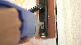 Die Arbeitskraft bohrt das Türschloss stockfotografie