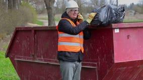Die Arbeitskraft, die am intelligenten Telefon spricht und hält Abfalltasche auf Abfallbehälter stock footage